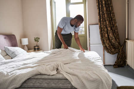 Middle aged man doing his morning routine at the bedroom