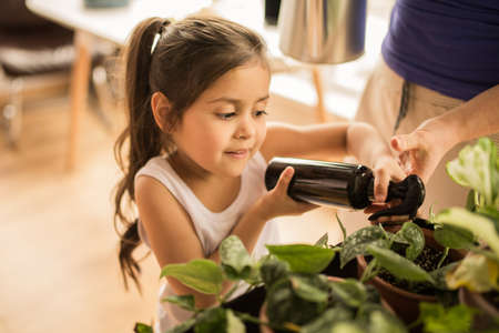 Girl holding spray with water and watering flowers at the pots at the morning
