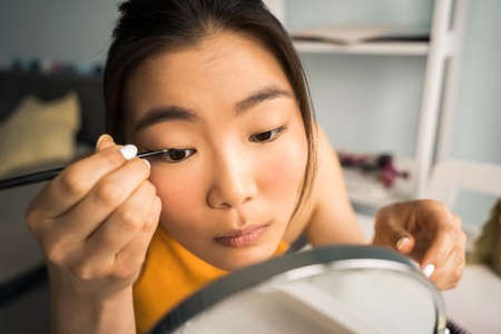 Girl sitting at the table in front of the mirror while preparing to doing makeup
