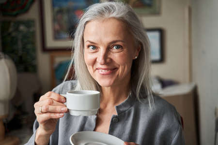 Woman drinking her morning tea and looking at the camera Imagens