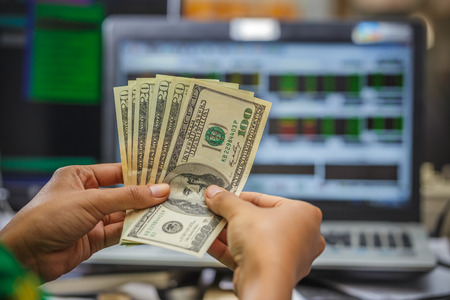 stock ticker board: Hand holding money with laptop display of stock market monitor on the background