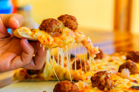 cooked pepper ball: hand holding a slice of pizza with sticky cheese Stock Photo