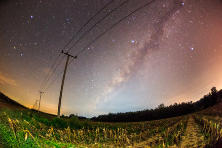 fish eye lens: long exposure photography of abstract night sky with stars and milky way over the power line in distortion of fish eye lens Stock Photo