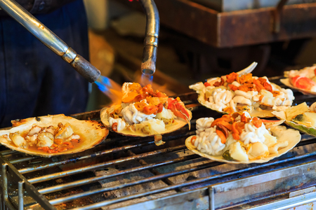 noix saint jacques: grilled seafood on seashell , japanese street food at Tsukiji Fish Market, Japan. selective focus Banque d'images