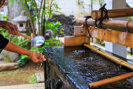 Unidentified Japanese people washing hand at bamboo fountain before giving the worship at the shrine