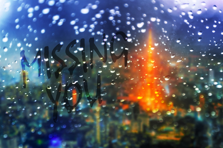 abstract message missing you written on glass window with rain drop and blurred city light background 스톡 콘텐츠