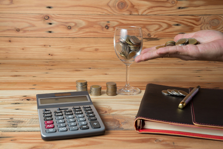 Coins in stacks, in a glass and a handful with calculator and an organizer on a wooden table, saving money for business concept
