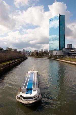 バック グラウンドで近代的な建物と、大阪の川の風光明媚なクルーズ船。