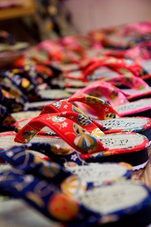 カラフルな日本語スリッパは日本の京都で有名な清水寺の近くの通りで販売されます。 写真素材