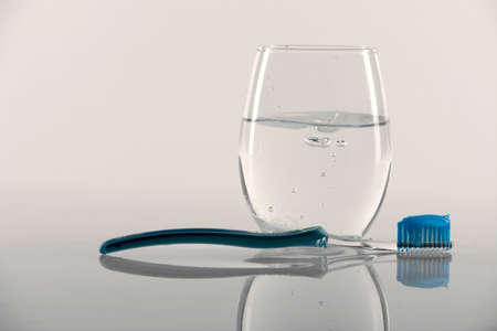 Toothbrush with toothpaste, glass of water on the background