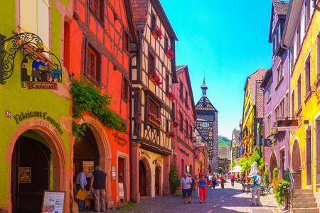 Riquewihr, France-June 23, 2016: Tourists are walking on the main shopping street; Rue du General de Gaulle, in Riquewihr, Alsace France Editorial