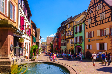 wine road: Riquewihr, France-June 23, 2016: Tourists are walking on the main shopping street; Rue du General de Gaulle, in Riquewihr, Alsace wine road