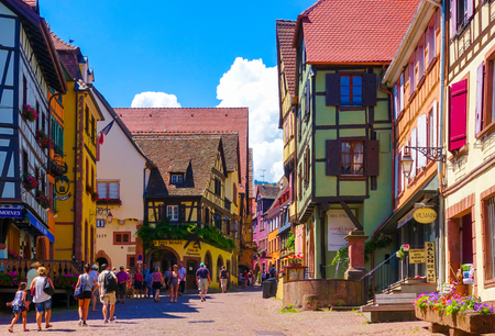half timbered house: Riquewihr, France-June 23, 2016: Tourists are walking on the main shopping street; Rue du General de Gaulle, in Riquewihr, Alsace wine road