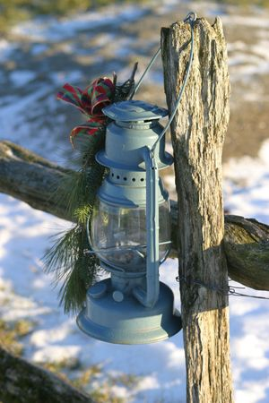 An old oil lamp hanging from a wood fence post, some snow in the background. Stock Photo - 249106