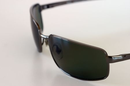 Close-up view of sunglasses sitting on a white surface, viewed from above. Stock Photo