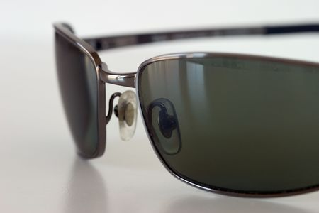 Macro view of sunglasses sitting on a white surface.