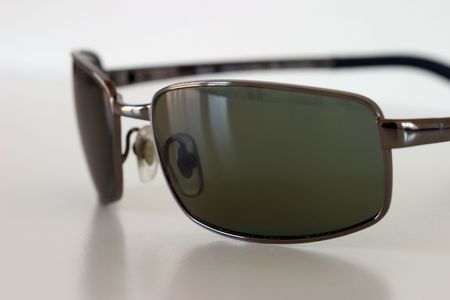 Sunglasses on a white surface, macro view.