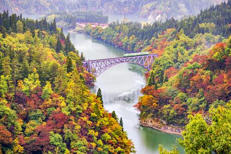 JR Tadami Line Train on the First Bridge across Tadami River in Autumn, Fukushima, Japan Фото со стока