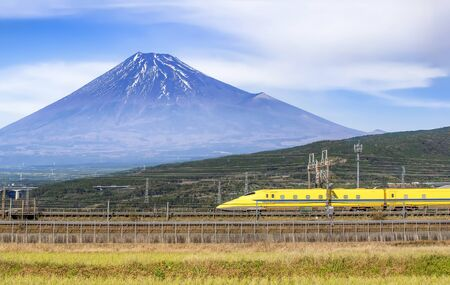 Yellow High Speed Bullet Train passing Fuji Mountain background, Shizuoka, Japan