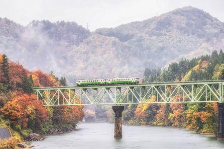 JR Tadami Line Train on the Bridge across Tadami River with Colorful maple tree in Autumn, Fukushima, Japan