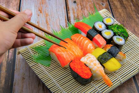 Hand keeping Sushi on Bamboo Plate with wooden background