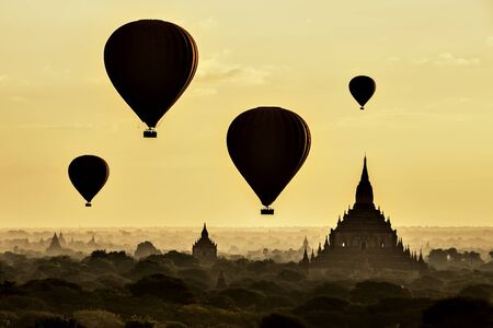 Tourist Balloons Flying over Great Pagoda with Morning Mist at Sunrise, Bagan, Myanmar Foto de archivo