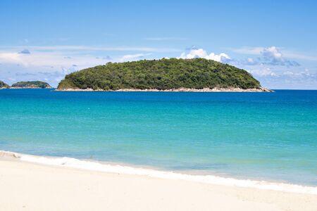 Turquoise Sea and White Sand Beach at Nai Harn Beach with Ko Man Island Background in Summer, Phuket, Thailand