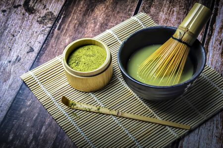 Green Tea Matcha Powder in the Bamboo Cup with Wooden Chasen in Matcha Tea Bowl and Wooden Spoon and on Wooden Background Foto de archivo - 149264034