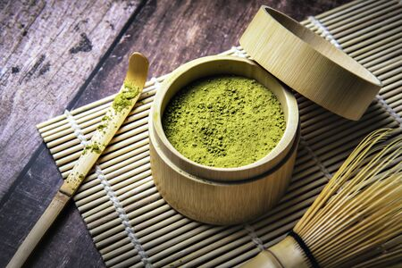 Green Tea Matcha Powder in the Bamboo Cup with Wooden Chasen and Wooden Spoon and on Wooden Background Foto de archivo