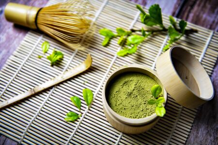 Green Tea Matcha Powder in the Bamboo Cup with Wooden Chasen in Matcha Tea Bowl and Wooden Spoon and on Wooden Background