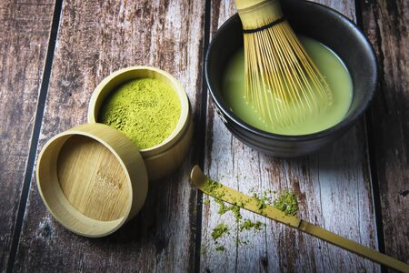 Green Tea Matcha Powder in the Bamboo Cup with Wooden Chasen in Matcha Tea Bowl and Wooden Spoon and on Wooden Background Foto de archivo - 149264085