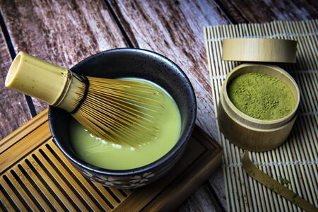 Green Tea Matcha Powder in the Bamboo Cup with Wooden Chasen in Matcha Tea Bowl and Wooden Spoon and on Wooden Background Foto de archivo - 149264113