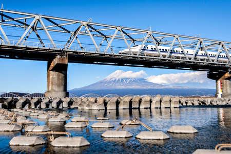 High Speed Bullet Train Shinkansen Tokaido Line ran on the Bridge over Fuji River with Fuji Mountain Background in Winter, Fuji City, Shizuoka Editorial