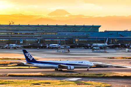 ANA Aircraft taxiing on the runway of Haneda International Airport with Fuji Mountain Background, Tokyo Editorial