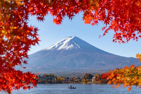 Fuji Mountain and Fisherman Boat in Autumn Red Maple Leaves Frame at Kawaguchiko Lake, Japan