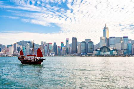 Hong Kong - December 18, 2019 : Duk Ling Tourist Junk Ship cruising in Victoria Harbour with Skyscraper Buildings of Hong Kong Background, Hong Kong