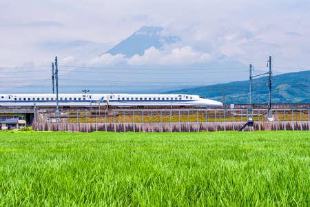 Japan - July 15, 2019 : High Speed Bullet Train Shinkansen ran on the railway passing Green Rice Field in Summer with Fuji Mountain Background, Shizuoka Editorial
