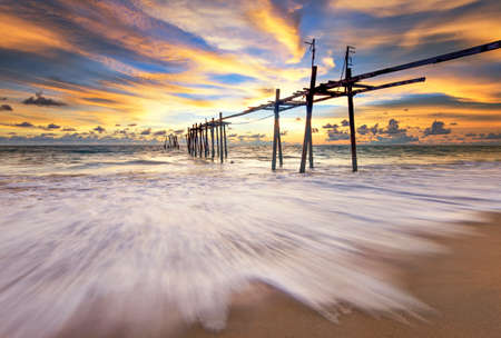 Wreckage Wooden Bridge of Old Pier with Twilight Sky at Sunset, Pilai Beach, Phang-gna, Thailand Foto de archivo - 153423719
