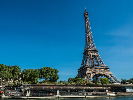 Eiffel Tower on Seine River side. Travel boat standby for traveler to go along river.