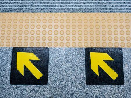 Yellow arrow sign on floor in subway. Stock fotó