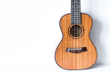 Brown ukulele on a white background.