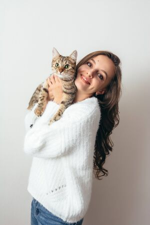 Girl in a white sweater hugs a gray cat on a white background.