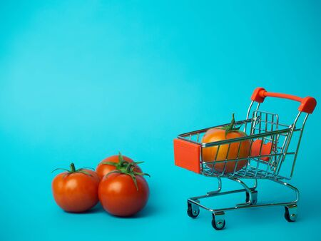 Small trolley with tomatoes on a blue background.