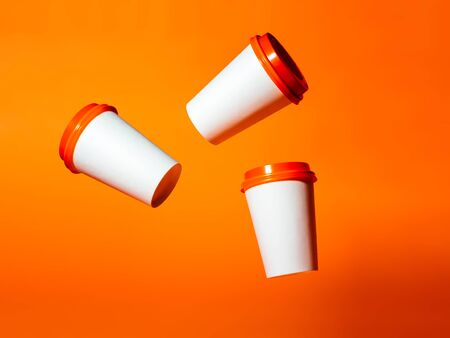 Three white paper cups with red lids hang in the air on an orange background. Фото со стока