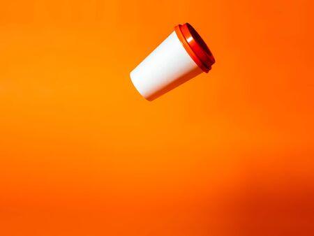 White paper cup drops on an orange background. Фото со стока