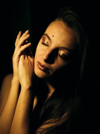 Young caucasian girl with golden make-up in the dark.
