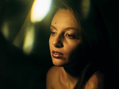 Young caucasian girl with golden make-up in the dark. Standard-Bild