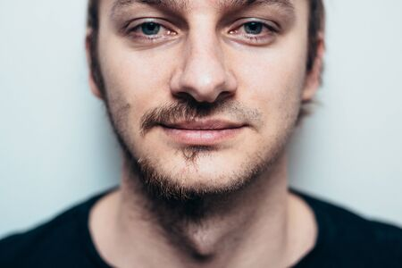 A close portrait of a shaved man on one side only.