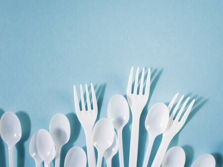 Plastic dishes, disposable tableware, plates, glasses, spoons, forks on a blue background. Caring for the environment. The problem is recycling. Reuse, safe planet, environmental concept. Trash.
