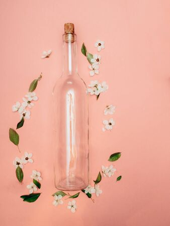 Transparent wine bottle not pink background with cherry blossoms. Flat lay. Copy space.